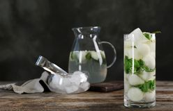 Glass with tasty melon ball drink. On wooden table royalty free stock images