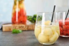 Glass with tasty melon ball drink. On table stock photos
