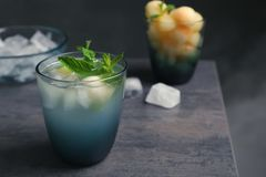 Glass with tasty melon ball drink on table against dark background. Space for text stock photos