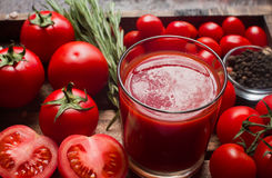 Glass of tasty organic tomato juice and fresh tomatoes and herbs on wooden tray Royalty Free Stock Image