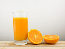 The glass of tasty pure orange juice and fresh orange half on wooden tray Stock Photography