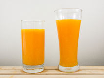 The glass of tasty pure orange juice on wooden tray Royalty Free Stock Image