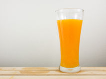 The glass of tasty pure orange juice on wooden tray Royalty Free Stock Photo