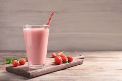 Glass with tasty strawberry smoothie. On wooden table royalty free stock photos
