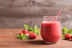 Glass with tasty strawberry smoothie. On wooden table royalty free stock image