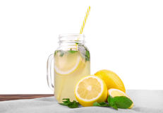 A glass with a tasty and useful cocktail from a juicy bright yellow lemon and fresh mint isolated on a white background. Royalty Free Stock Photography