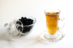 A glass of tea. With a bowl of raisin Royalty Free Stock Photography
