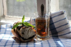 Glass of tea and a bun. With poppy seeds Stock Photo