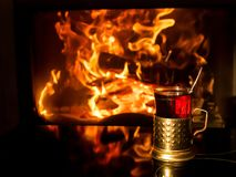 Glass of tea in the Cup holder by the fireplace royalty free stock photos