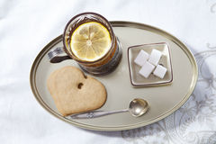 Glass of tea in the cup holder,  saucer with a lemon on a white Royalty Free Stock Photos