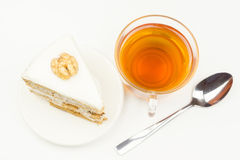 Glass tea Cup next to the piece of cake and a spoon. Glass tea Cup next to the piece of cake and a teaspoon Stock Photos
