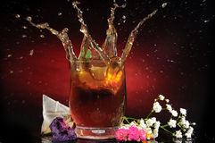 Glass with tea, flowers and nice reflections Stock Photography