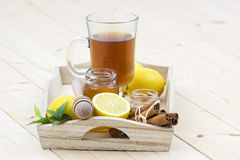 Glass of tea, honey, lemons and cinnamon sticks Royalty Free Stock Photo