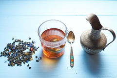 Glass of tea with jug and tea leaves Stock Image