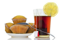 Glass with tea, a lemon and chocolate fruitcakes Royalty Free Stock Photography