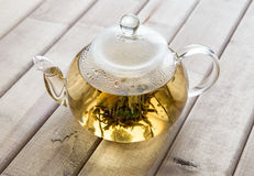 A glass tea pot with Flower Chinese tea on wooden background Stock Photos