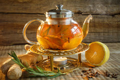 Glass tea pot with hot tasty tea with lemon, herbs,. Yellow lemo Stock Photography