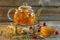 Glass tea pot with hot tasty tea with lemon, herbs,. Yellow lemo Stock Image
