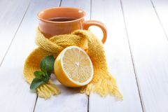 Glass of tea in a scarf. Healing glass of tea in a scarf on a wooden background stock photos