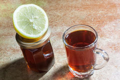Glass of tea with slice of lemon and bottle of honey. On a table Royalty Free Stock Images