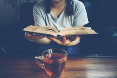 A glass of tea on table with woman reading book on sofa. Stock Photo