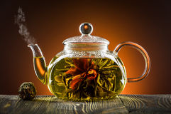 Glass teapot. With blooming tea flower on wooden table stock photography