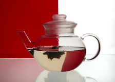 Glass teapot. With exotic floral tea on red background stock photos