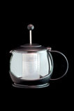 Glass Teapot Against Black. Glass teapot and infuser with plunger isolated against black Stock Photography