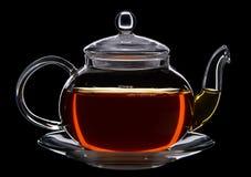 Glass teapot of black tea. Against black background stock photos