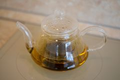 Glass teapot with blooming tea flower inside against wooden. Background Stock Photos