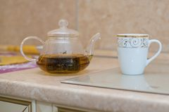 Glass teapot with blooming tea flower inside against wooden. Background Royalty Free Stock Photos