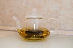 Glass teapot with blooming tea flower inside against wooden. Background Royalty Free Stock Images