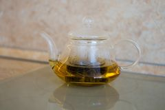 Glass teapot with blooming tea flower inside against wooden. Background Stock Photo