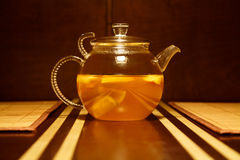 Glass teapot with citrus hot drink on brown wooden table. Glass teapot with yellow citrus hot drink on brown wooden table Stock Photos