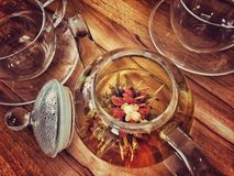 Glass teapot with colourful floral tea on wooden table with matching tea cups Stock Photography