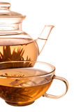Glass teapot and cup. With blooming flower green tea on white background royalty free stock image