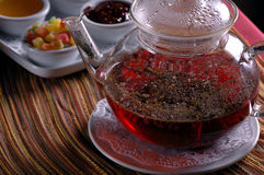 Glass teapot and cup with sweets stock photos
