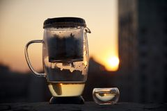 A glass teapot and a cup of tea. On a blurred background of the evening city in the light of sunset stock images