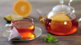 Glass teapot and cup with tea, next to which lies a bag of black tea with orange, lemon, lime and mint on wooden table. A beautiful composition of black tea and stock video