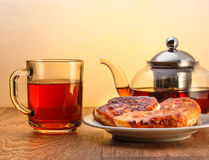 Glass teapot and cup with tea and plate of pancakes on wooden surface on yellow background Stock Photo
