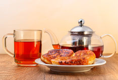 Glass teapot and cup with tea and plate of pancakes on wooden surface on yellow background Royalty Free Stock Images