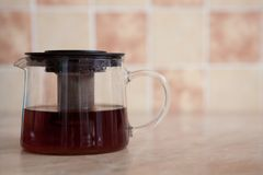 Glass teapot and glass cup with tea on the table.  Stock Photos