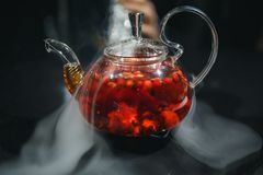 Glass teapot filled with flowers and berries, green tea. Appetizing beautiful drink in orange tones on a black background. Close stock images
