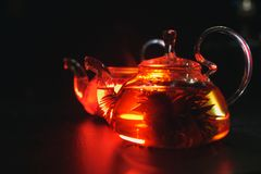 Glass teapot filled with flowers and berries, green tea. Appetizing beautiful drink in orange tones on a black background. Close royalty free stock photography