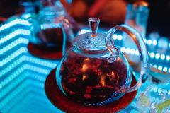 Glass teapot in the hookah room on the table with a mirror surface and neon lighting royalty free stock images