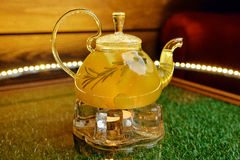 Glass teapot with hot pineapple tea with pineapple slices Stock Photos