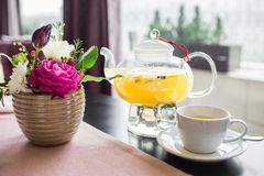 Glass teapot with hot pineapple tea with pineapple slices in a cafe. A cup of fragrant yellow tea, a glass teapot and beautiful pi Royalty Free Stock Images