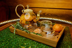 Glass teapot with hot tea with tangerines on a wooden tray Royalty Free Stock Images