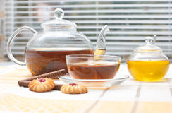 Glass teapot,  mug, honey jar and cakes Stock Photos