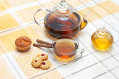 Glass teapot,  mug, honney jar and cakes Royalty Free Stock Images